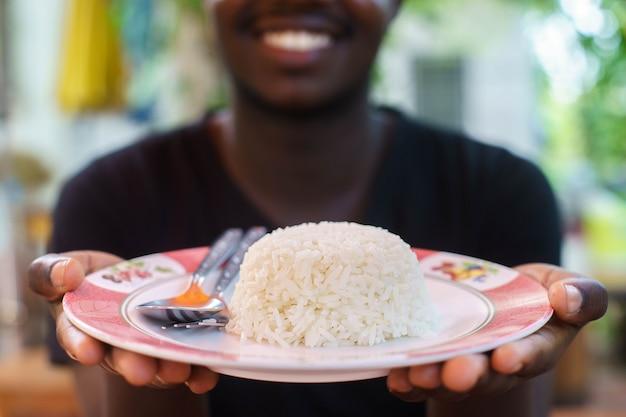 Hand van de afrikaanse mens die een witte rijst in de plaat houdt.