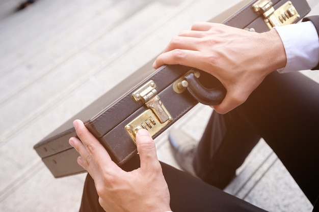 Hand van de aziatische bedrijfsmens die een aktentas, het concept van de zakenmanlevensstijl probeert te openen