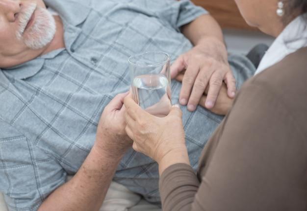 Hand van de aziatische hogere mens die geneesmiddelen en drinkwater nemen terwijl thuis op laag ligt