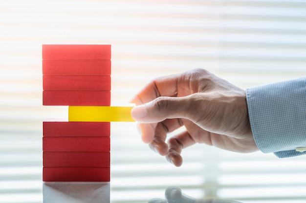 Hand van de bedrijfsmens die geel blok verwijdert uit stapel rode blokken. risicobeheer bedrijfsconcept.