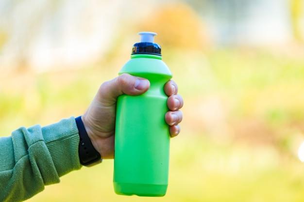 Hand van de jonge mens die de groene fles van het sportwater of reisfles houden.