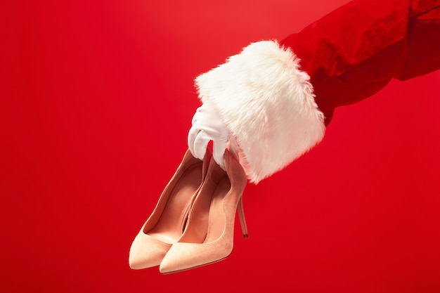 Hand van de kerstman met een damesschoenen op rode achtergrond. seizoen, winter, vakantie, feest, cadeau-concept