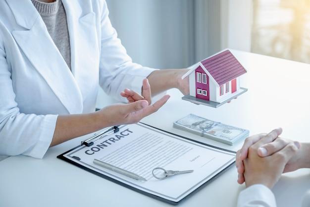 Hand van de makelaar legt het zakelijke contract uit, huur, koop, hypotheek, een lening
