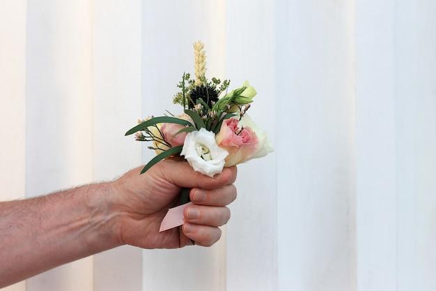 Hand van de man die een klein mooi boeket bloemen houdt