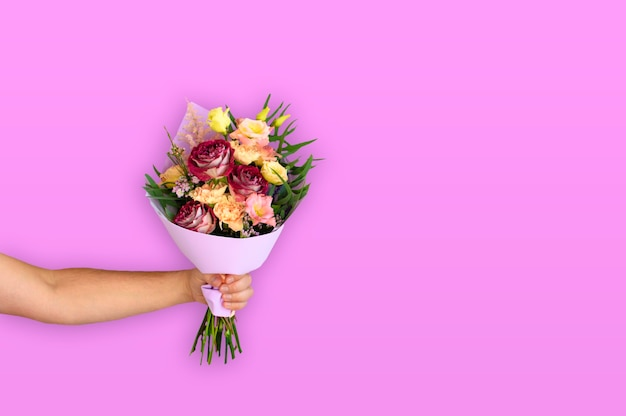 Hand van de man met een mooi boeket bloemen op roze