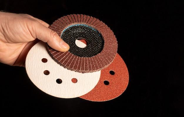 Hand van de meester greep flap disc en slijpschijf op zwarte achtergrond