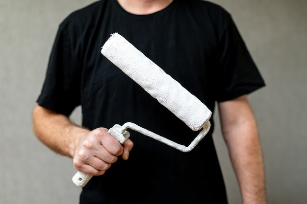 Hand van de meester met een roller voor het schilderen van muren of andere oppervlakken, constructie- of reparatieconcept