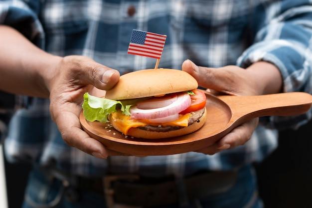 Hand van de mens die amerikaanse eigengemaakte hamburger houdt.