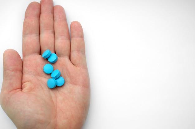 Hand van de mens die blauwe pillen houdt