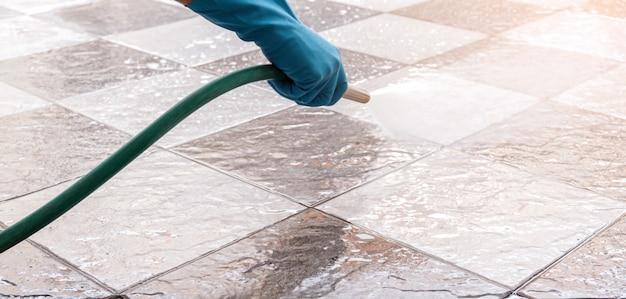 Hand van de mens die blauwe rubberhandschoenen draagt die een slang gebruiken om de tegelvloer schoon te maken.