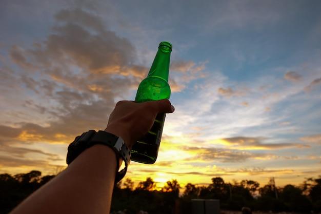 Hand van de mens die een groene bierfles op de zonsonderganghemel houdt