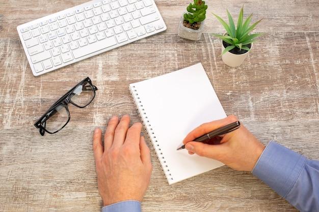 Hand van de mens die in witte spiraalvormige blocnote schrijft