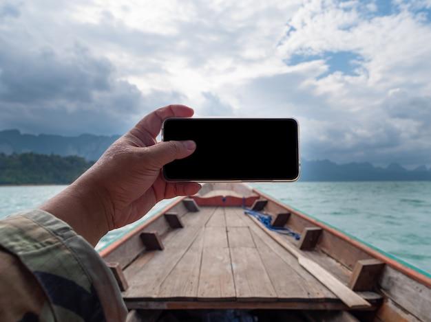 Hand van de mens die mobiele slimme telefoon met behulp van tegen toneellandschap van bootmening in de grote rivier en reservoirdam met berg en aardbos