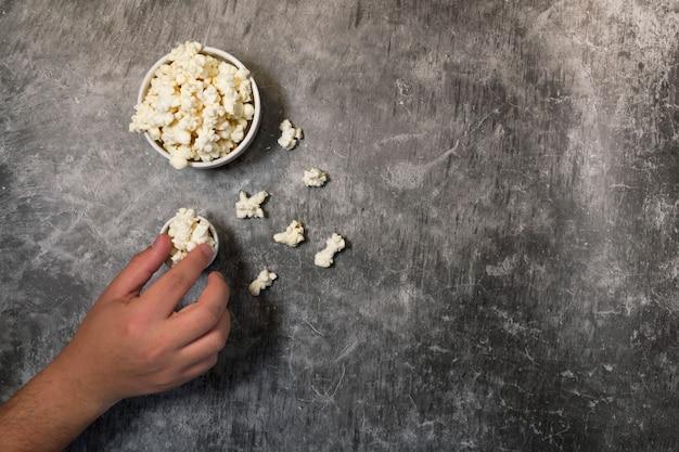Hand van de mens die popcorn, kommen met popcorn en grijze achtergrond eet. weekend- of avondplan