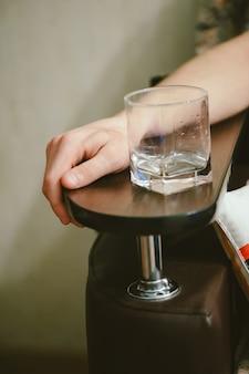Hand van de mens met een leeg glas whisky