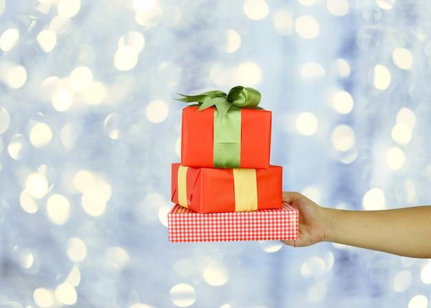 Hand van de mens met een rode doos van de kerstmisgift op grijze bokehachtergrond.