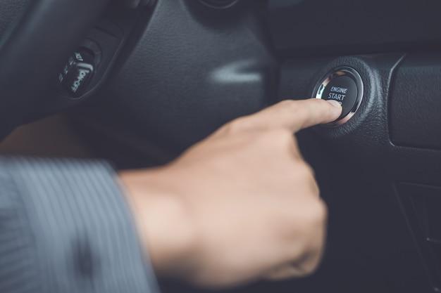 Hand van de mens op start / stop-knop in de moderne auto