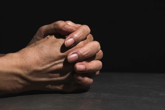 Hand van de mens tijdens het bidden voor religie.