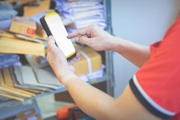 Hand van de mens wat betreft een scanner tijdens het gebruik voor werk in magazijn.
