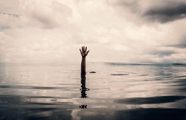 Hand van de mens wil helpen na verdrinken in het meer