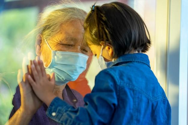 Hand van de oma en het kleinkind op een raamvlak, bescherming coronavirus en covid-19 pandemie, sociaal afstandsconcept.