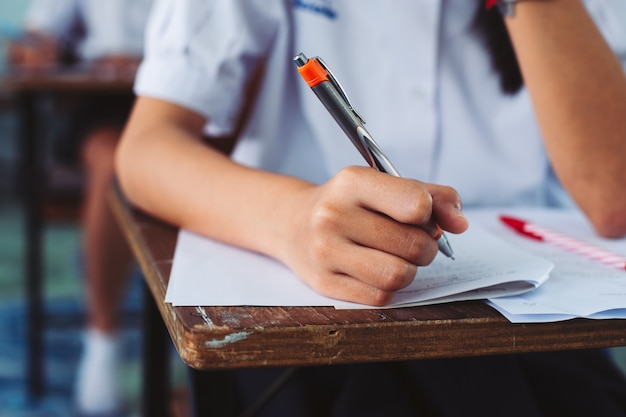 Hand van de pen van de studentenholding en het nemen van examen in klaslokaal met spanning
