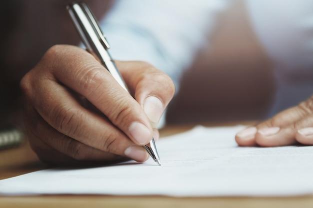 Hand van de pen van de vrouwenholding met het schrijven op document rapport in bureau