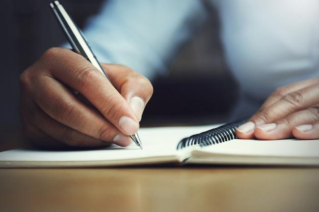 Hand van de pen van de vrouwenholding met het schrijven op notitieboekje in bureau