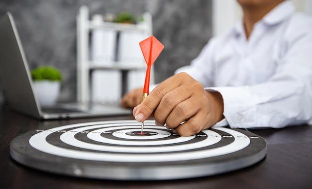 Hand van de pijl van de bedrijfsmensholding op doel met financieel millimeterpapier met laptop op lijst, succesvolle prestatie, succes en win concept