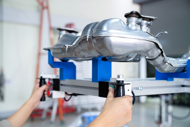 Hand van de productiemedewerker drukt op de knop van de machine om de onderdelen op te tillen, automotive p