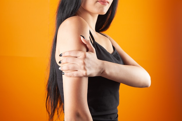 Hand van de vrouw doet pijn op oranje achtergrond
