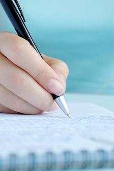 Hand van de vrouw het schrijven van vermeldingen in een notitieblok