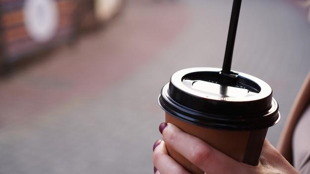 Hand van de vrouw met een kopje koffie buiten tegen de achtergrond van de stoep van de stad