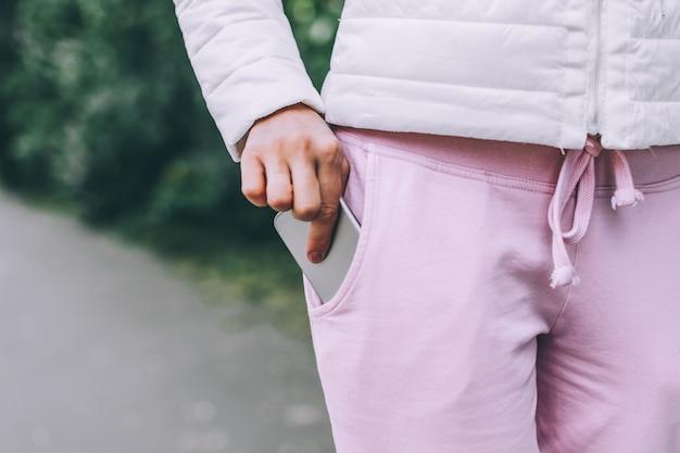 Hand van de vrouw stopte smartphone in niet-ritsvak op broek.