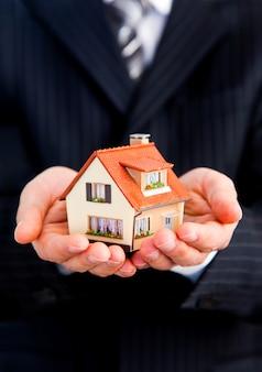 Hand van de zakenman met het huis.