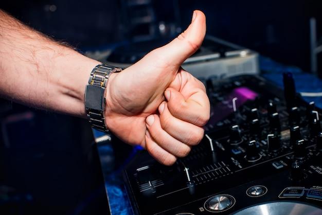 Hand van dj shows duimen omhoog. schakelaars en afstandsbediening in nachtclub