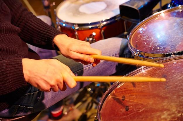 Hand van drummer met stokken en drums