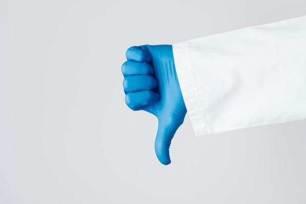 Hand van een arts in blauwe handschoen met afkeuring duim omlaag teken geïsoleerd op een witte pagina