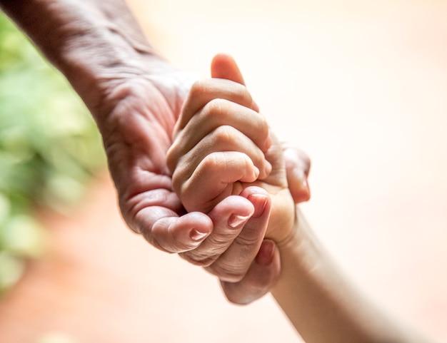 Hand van een bejaarde die de hand van een kind houdt