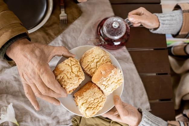 Hand van een bejaarde man die een vers, zelfgemaakt broodje van een bord neemt dat door zijn zorgvuldige vrouw aan de tafel wordt vastgehouden terwijl ze allebei aan het ontbijten zijn