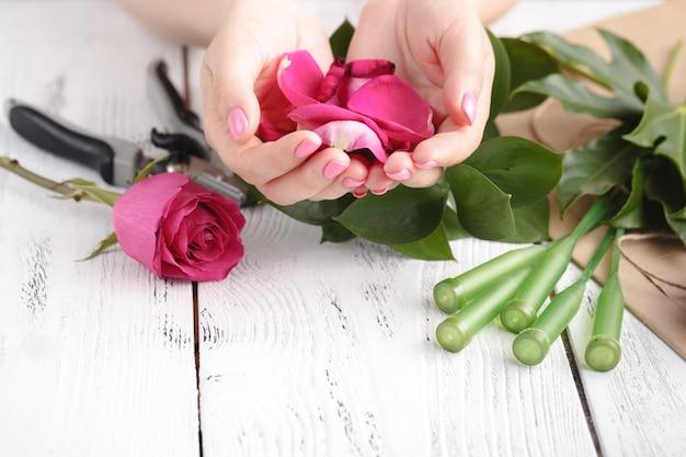 Hand van een bloemist vrouw vol met rozenblaadjes voor bruiloft