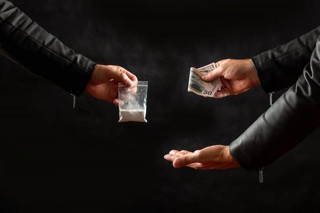 Hand van een drugsverslaafde met geld dat een dosis cocaïne koopt