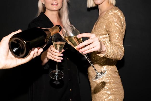 Hand van een jonge man met een fles champagne en de drank in fluiten gieten die vastgehouden worden door twee elegante vrouwen tijdens de viering
