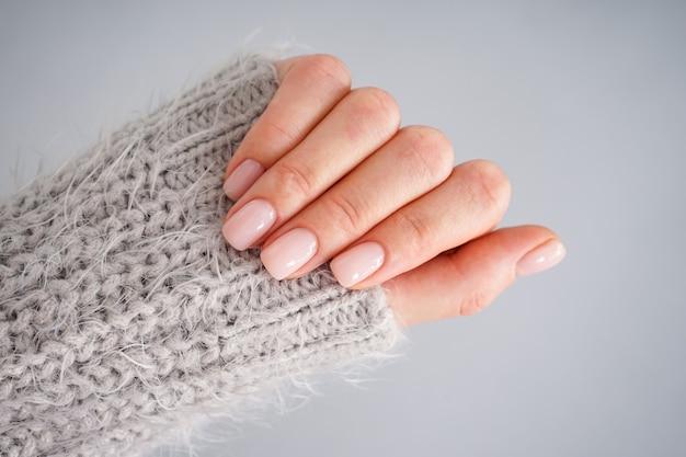Hand van een jonge vrouw met mooie manicure op een grijze achtergrond. plat leggen, close-up. vrouwelijke manicure.
