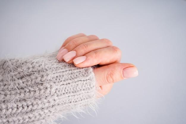 Hand van een jonge vrouw met mooie manicure op een grijze achtergrond. vrouwelijke manicure. plat leggen