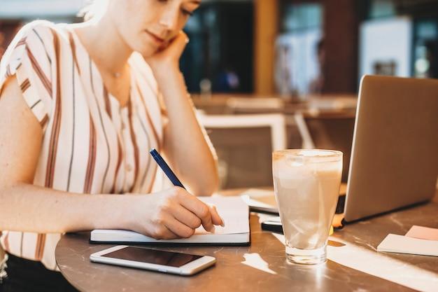 Hand van een jonge vrouwelijke bedrijfsvrouw die op een notitieboekje op een lijst buiten schrijft.