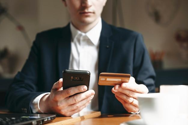 Hand van een jonge zakenman met een gouden creditcard en een smartphone zittend op tafel binnen.