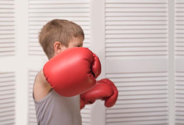 Hand van een jongen in een rode bokshandschoen.