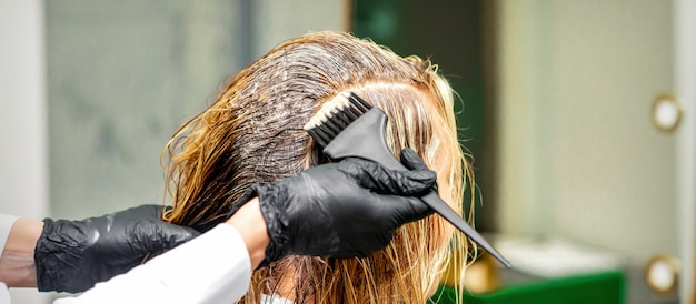 Hand van een kapper in zwarte handschoenen die kleurstof aanbrengt op het vrouwelijke haar in een schoonheidssalon