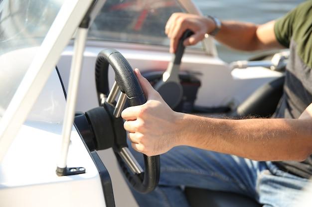 Hand van een man aan het stuur van een motorboot